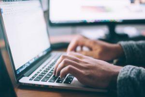 man writing on a laptop