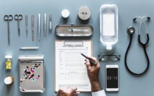 medical checklist, glasses, pills, scalpels and other medical tools on a table