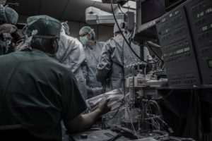 operating room with a group of doctors standing around the operating table