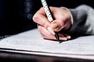 a hand holding a pen and writing something