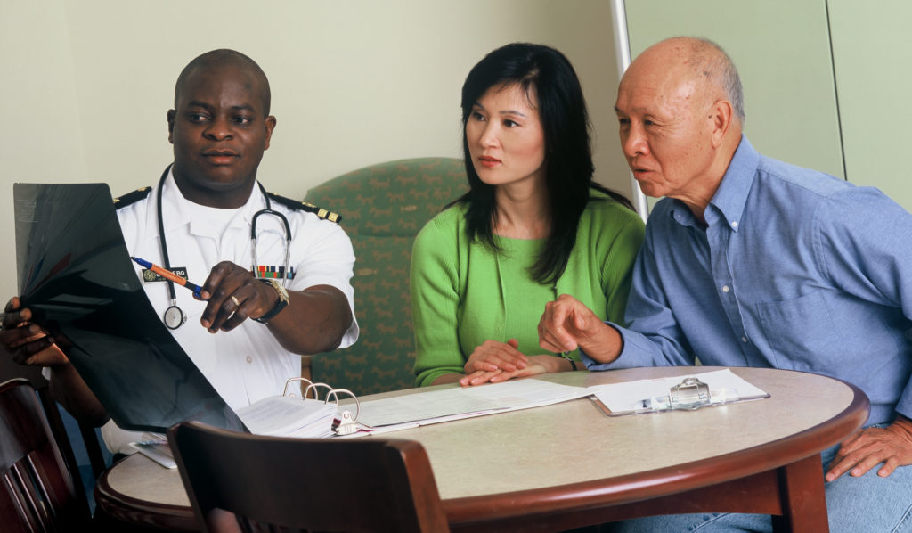 an african american doctor talking to an asian couple